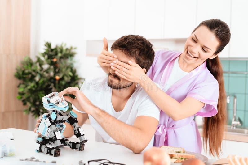 En man samlar en robot i köket Hans flickvän kom till honom bakifrån och täcker försiktigt henne ögon med hennes händer fotografering för bildbyråer