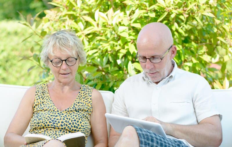 En man ser en digital minnestavla, och hans fru läser en bok royaltyfria foton