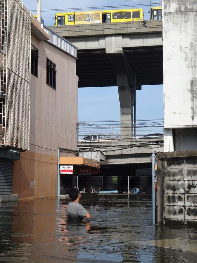 En man ser skadan i en översvämmad gata i Rangsit, Thailand, i Oktober 2011 Några bilar parkeras säkert på en bro arkivbilder