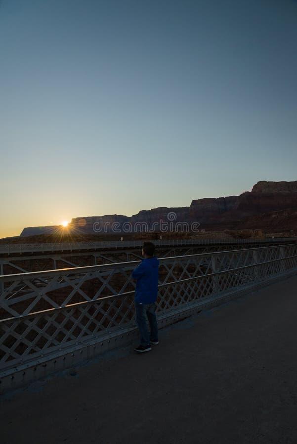 En man ser solnedgång på Navajobron i Arizona USA arkivbild