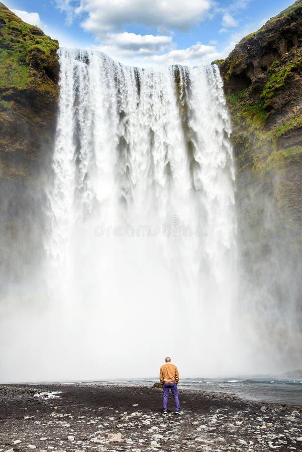 En man ser storheten av vattenstrålar i en vattenfall Skogafoss i Island Exotiska länder F?rbluffa st?llen arkivfoton