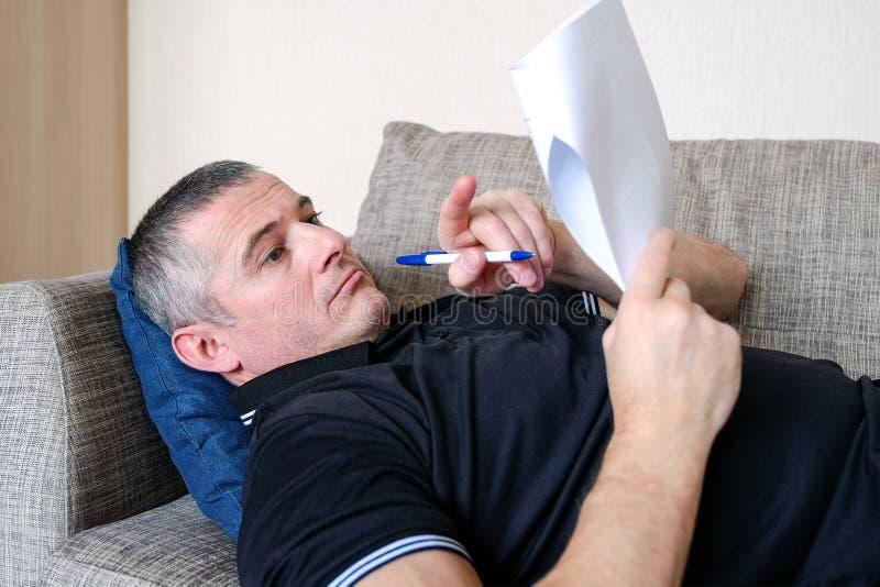 En man ser till och med affärsdokument, rapporter Olustkänsla arbete i hem- miljö arkivbild