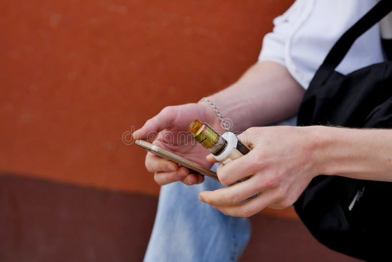 En man sitter med en telefon och vaping fotografering för bildbyråer