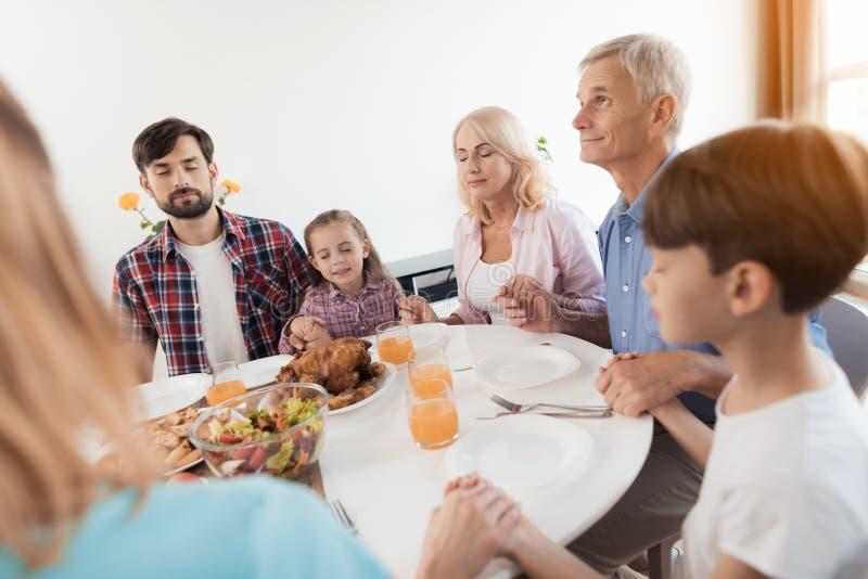 En man sitter på en festlig tabell för tacksägelse och ser upp Han ber med hans familj royaltyfria bilder