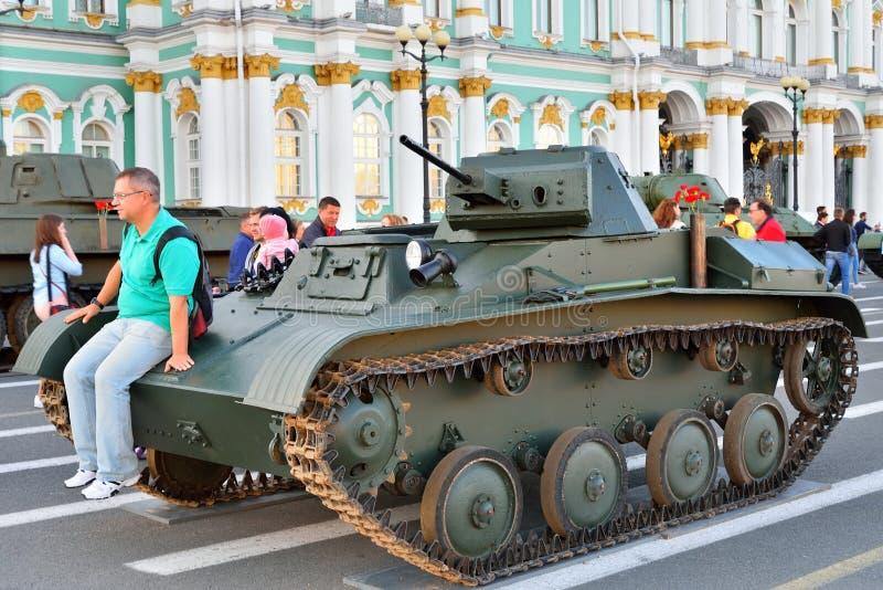 En man sitter på huven av den sovjetiska lilla amfibiska behållaren T-38 arkivfoto