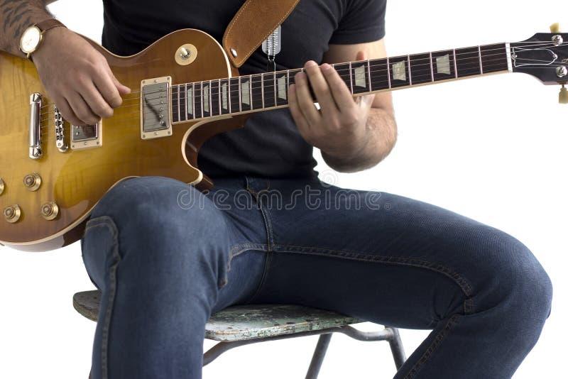En man sitter på en stol och spelar en elektrisk gitarr på en vit bakgrund arkivfoton