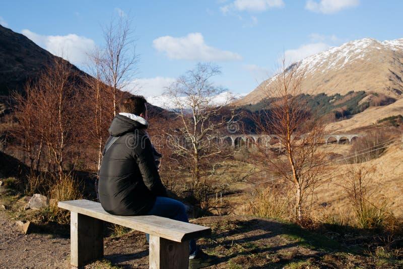 En man sitter på en träbänk som ser den Glenfinnan viadukten, Skottland arkivfoto