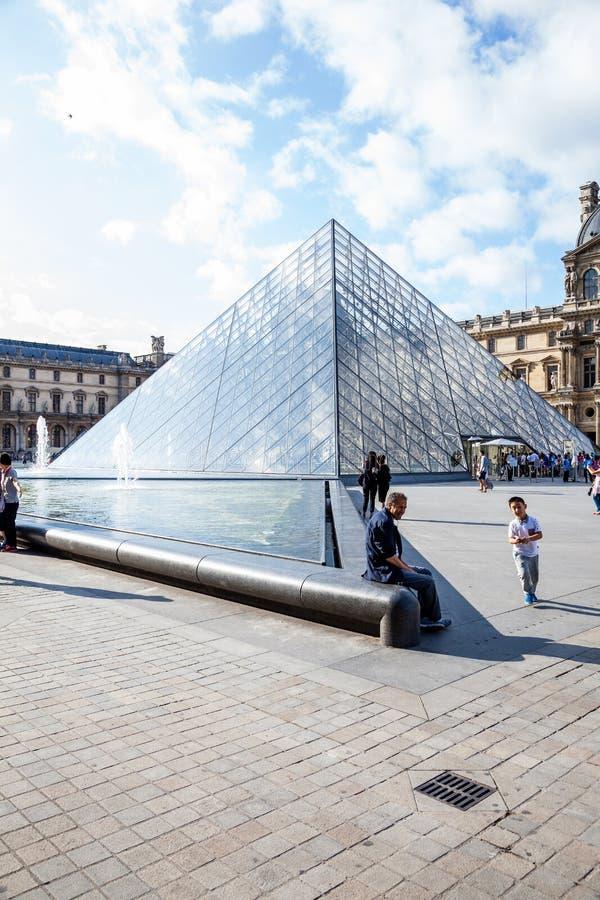 En man sitter på vattensärdraget bredvid ingången till Louvre royaltyfria foton