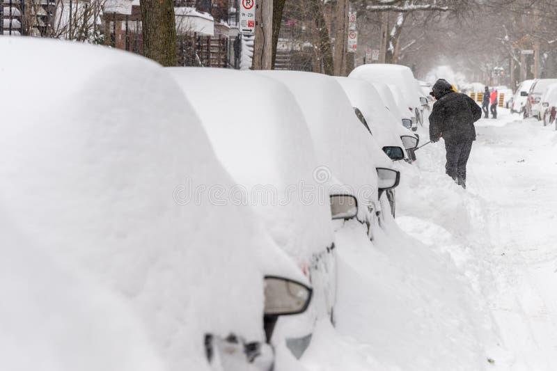 En man skyfflar snö för att frigöra hennes fastnade bil arkivfoto