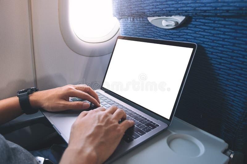 En man som använder och skriver på bärbar datordatoren med den vita skrivbords- skärmen för mellanrum, medan sitta i kabinen fotografering för bildbyråer