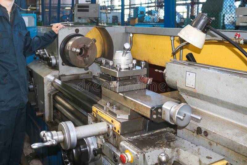 En man som arbetar i en ämbetsdräkt, overaller står bredvid en industriell drejbänk för att klippa, roterande knivar från metalle royaltyfri bild
