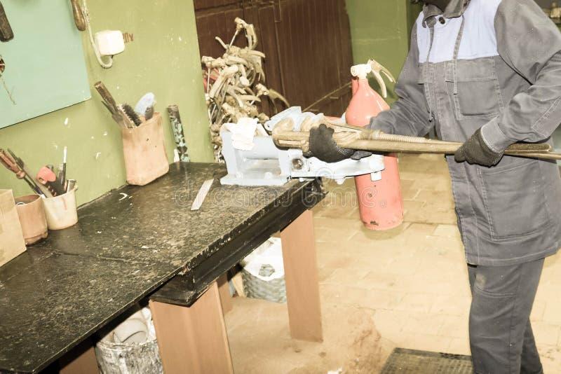 En man som arbetar industriell last med en enorm gasskiftnyckel, skruva av en mutter på en röd brandsläckarecylinder i ett fabrik fotografering för bildbyråer