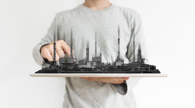 En man som arbetar på den digitala minnestavlan, med kraftverket, hologram för byggnader för oljeraffinaderibranschfabrik arkivbilder