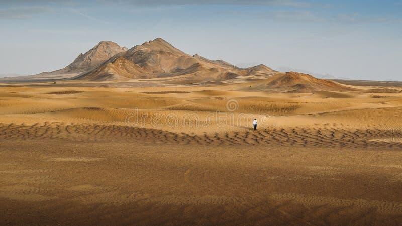 En man som bara går i Dashten-e-Lut, en stor salt öken som lokaliseras i landskapen av Kerman, Sistan och Baluchestan royaltyfri fotografi