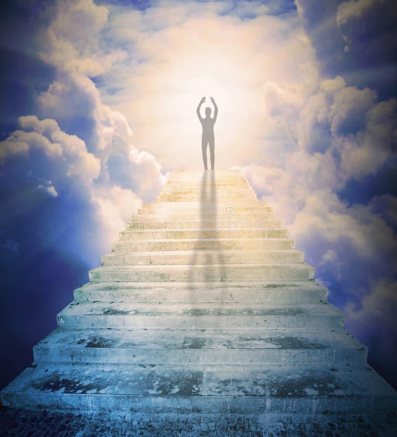 En man som ber mot porten till paradiset arkivbild