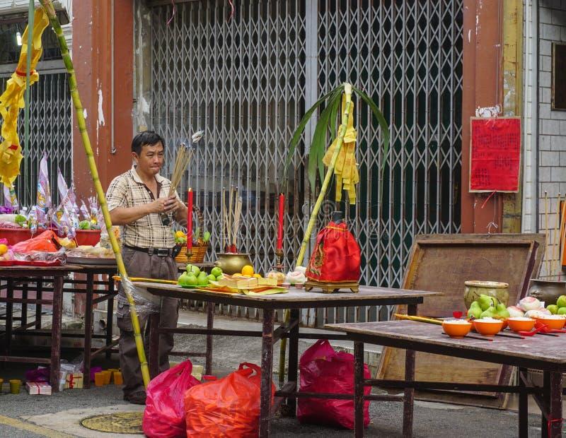 En man som ber på gatan på kineskvarteret i Melaka, Malaysia royaltyfria foton
