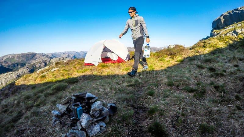 En man som campar i vildmarken med en flaska av vatten i hans hand Norge Preikestolen royaltyfri fotografi