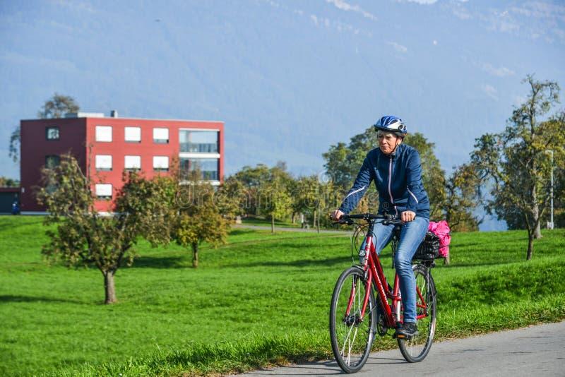 En man som cyklar på den lantliga vägen i Lucerne royaltyfri bild