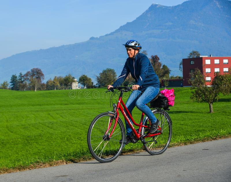 En man som cyklar p? den lantliga v?gen i Lucerne royaltyfri bild