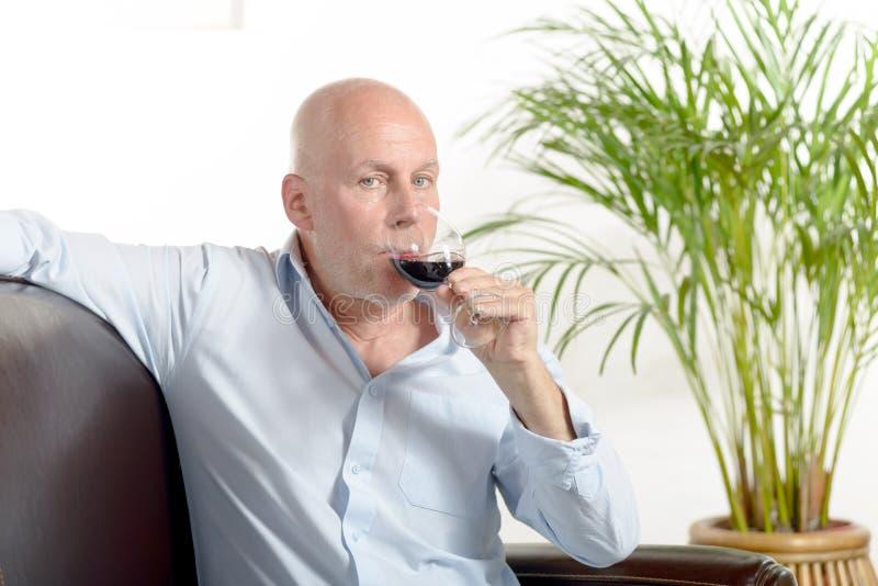 En man som dricker ett exponeringsglas av rött vin royaltyfri foto