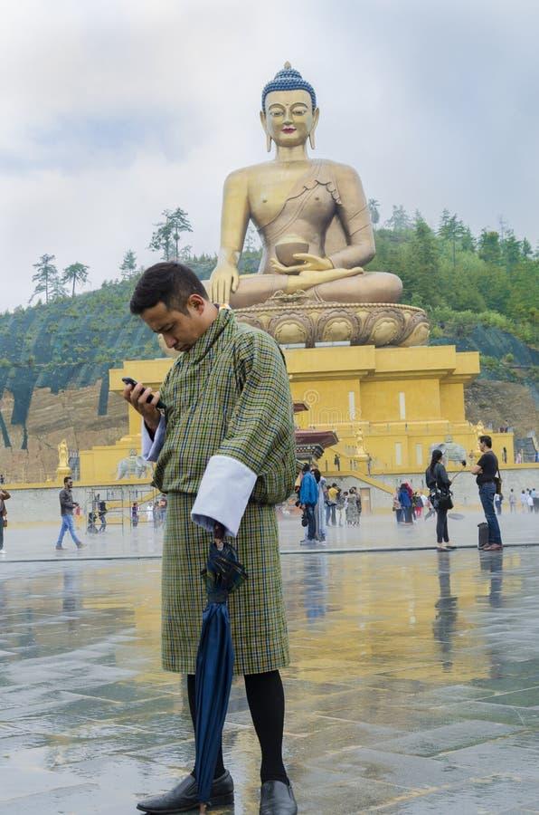 En man som framme står av den stora Buddhastatyn arkivbild