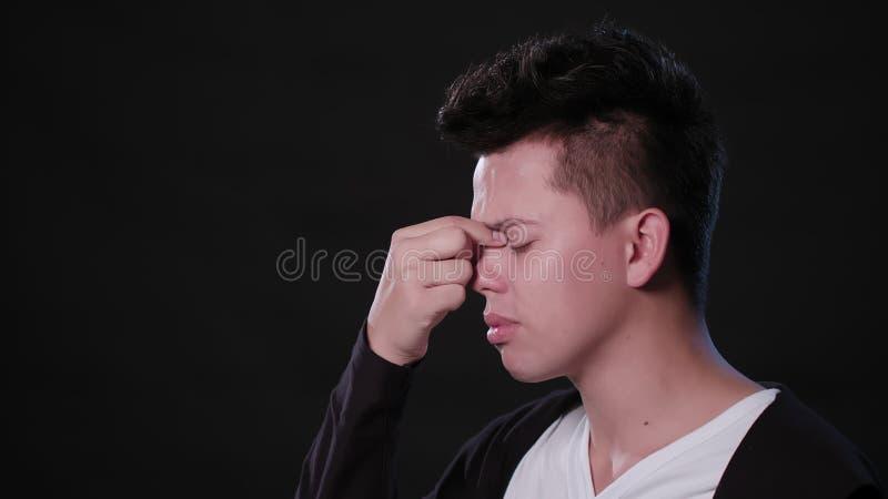 En man som imiterar huvudvärk mot en svart bakgrund arkivbilder