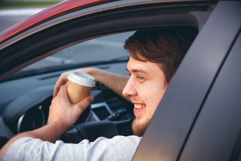 En man som kör en bil som dricker kaffe fotografering för bildbyråer