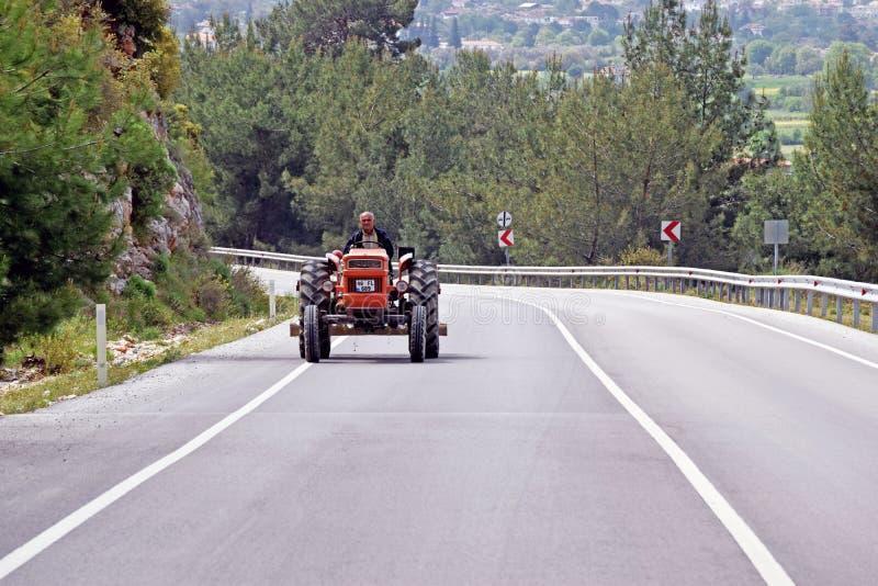 En man som kör en röd bogserare längs en huvudväg royaltyfri foto