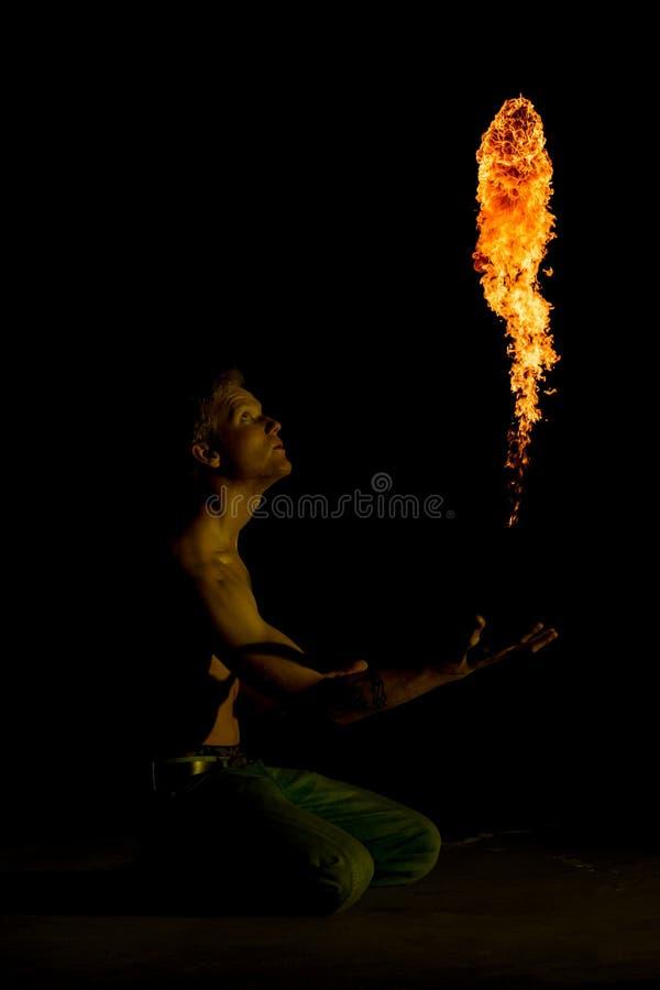 En man som kastar en boll av brand arkivfoto