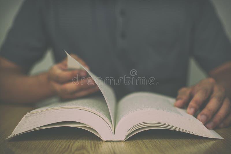 En man som läser en bok på trätabellen, medan bläddra sidorna med tappning, filtrerar suddig bakgrund fotografering för bildbyråer