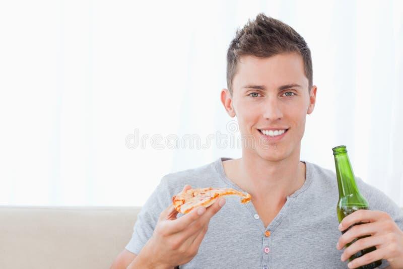 En man som ler med öl i en, räcker och pizza i annan royaltyfri foto