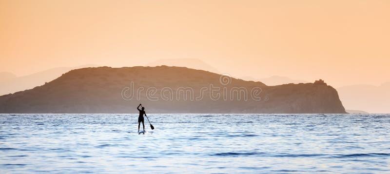 En man som paddlar på en paddleboard i det öppna havet fotografering för bildbyråer