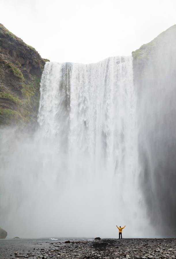 En man som poserar på den Skogafoss vattenfallet royaltyfri bild
