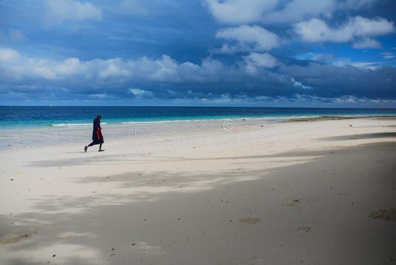 En man som promenerar stranden arkivbild