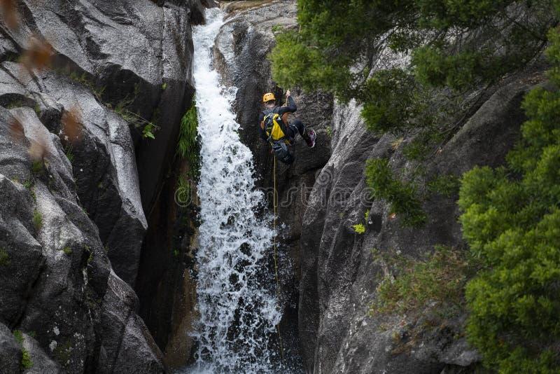 En man som rappelling den Arado vattenfallcascataen att göra arado i den Peneda Geres nationalparken arkivfoton
