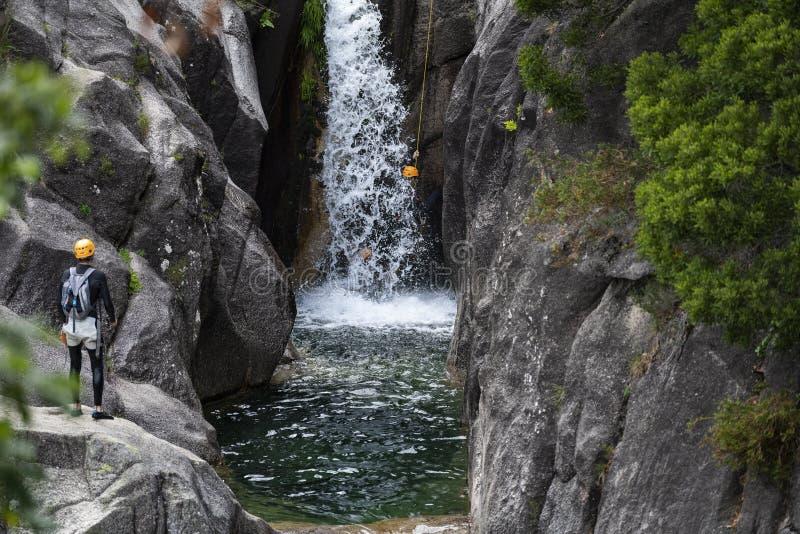 En man som rappelling den Arado vattenfallcascataen att göra arado i den Peneda Geres nationalparken royaltyfria foton