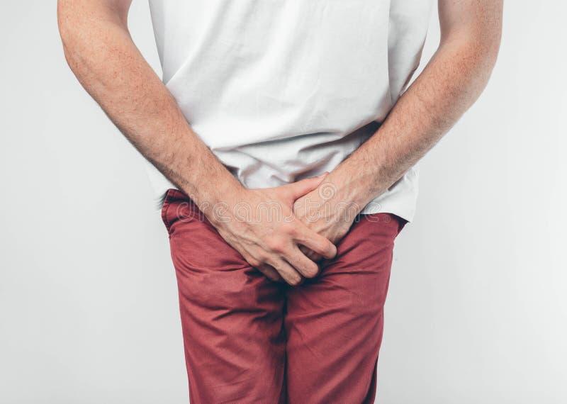 En man som rymmer hans penis med på den vita bakgrunden Önskar att gå till toaletten arkivfoton