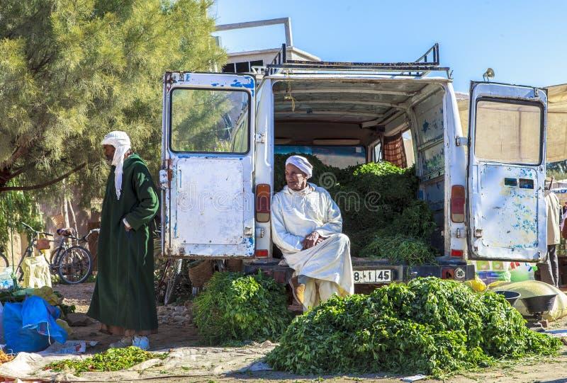 En man som säljer grönsaker i den svarta marknaden, Marocko arkivfoto