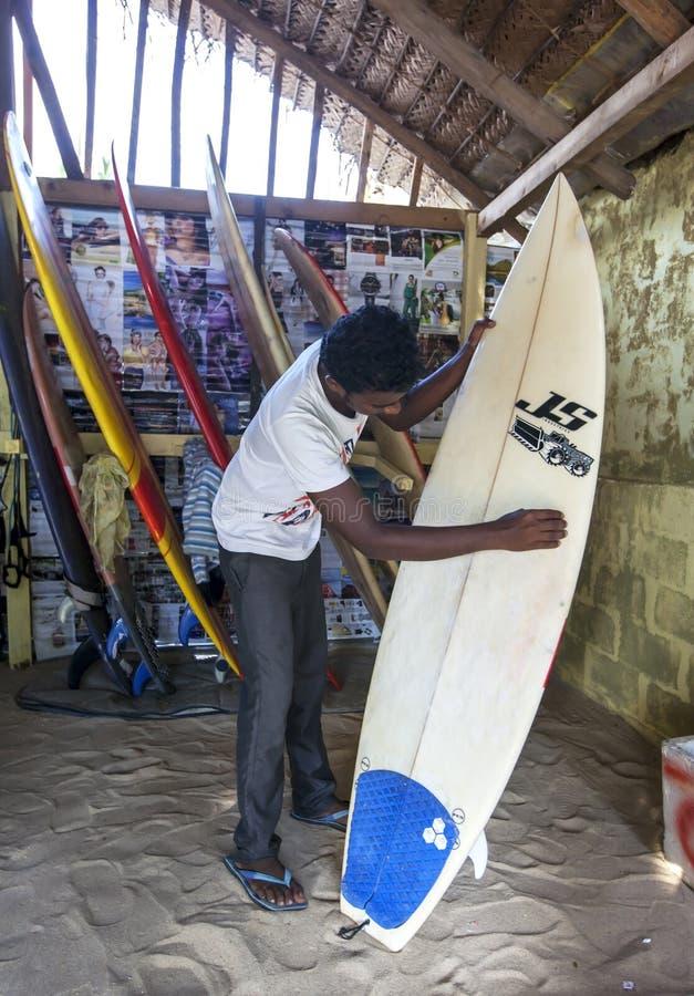 En man som sandpapprar en surfingbräda royaltyfri bild