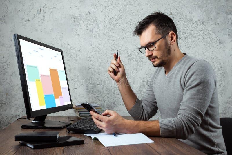 En man, en man som sitter på en tabell i kontoret som arbetar på viktig legitimationshandlingar Begreppet av kontorsarbete kopier arkivbild