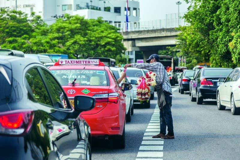 En man som som säljer blommagirlanden till en taxi arkivbild