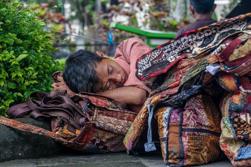 En man som sover på gatan Yogyakarta i Indonesien royaltyfria bilder