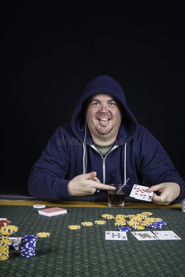 En man som spelar pokersammanträde på bluffa för tabell arkivfoto