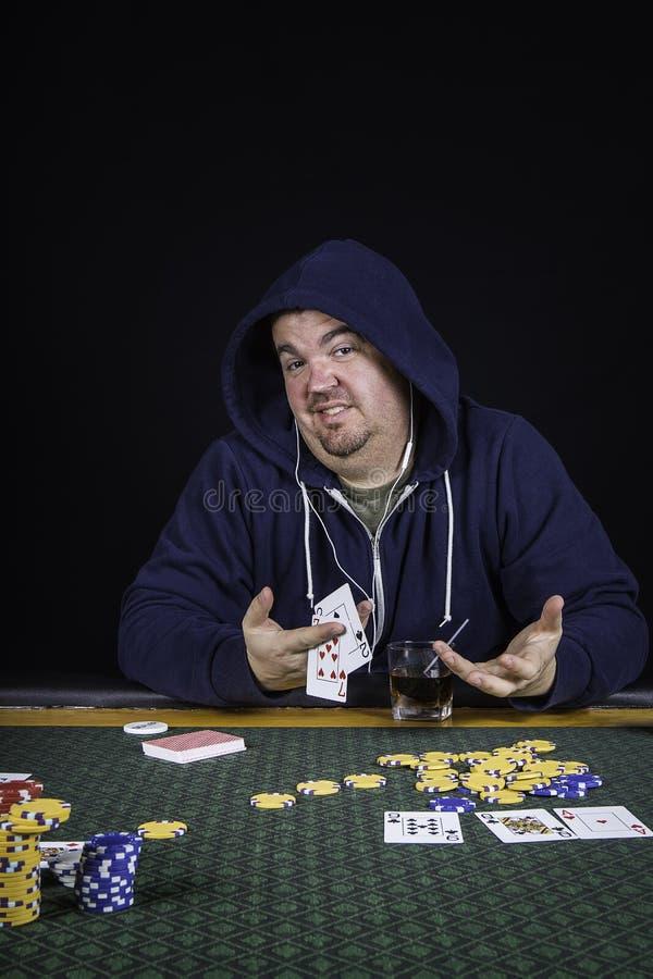 En man som spelar pokersammanträde på bluffa för tabell royaltyfria bilder