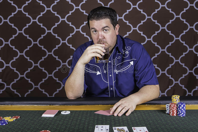 En man som spelar pokersammanträde på en tabell royaltyfria foton