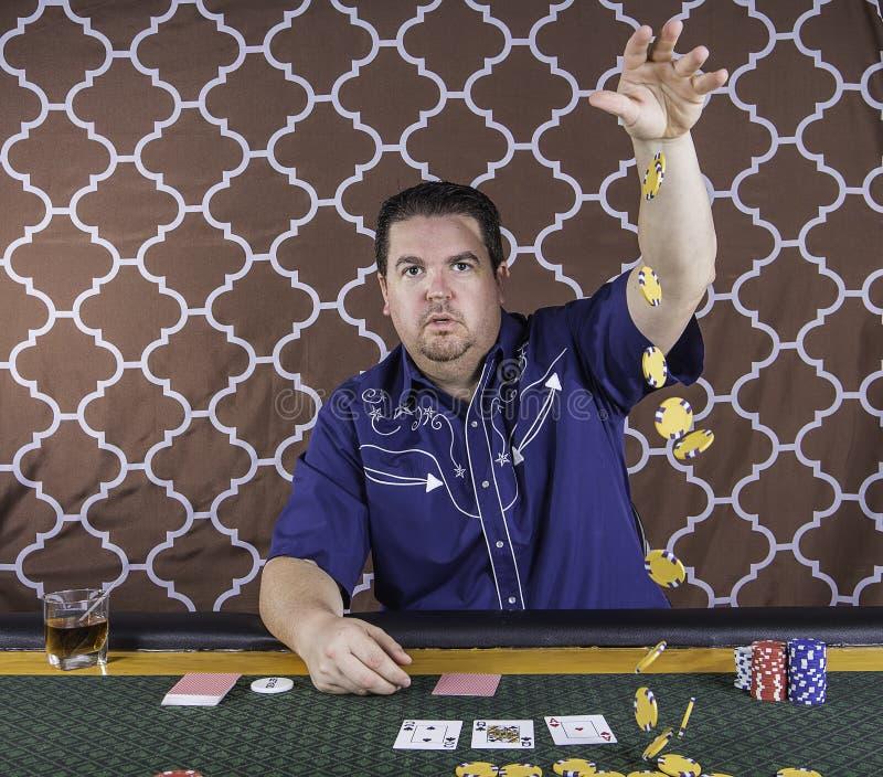 En man som spelar pokersammanträde på en tabell royaltyfria bilder