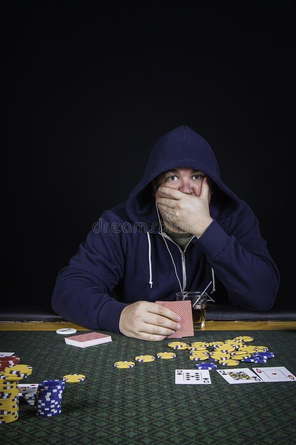 En man som spelar pokersammanträde på en tabell fotografering för bildbyråer