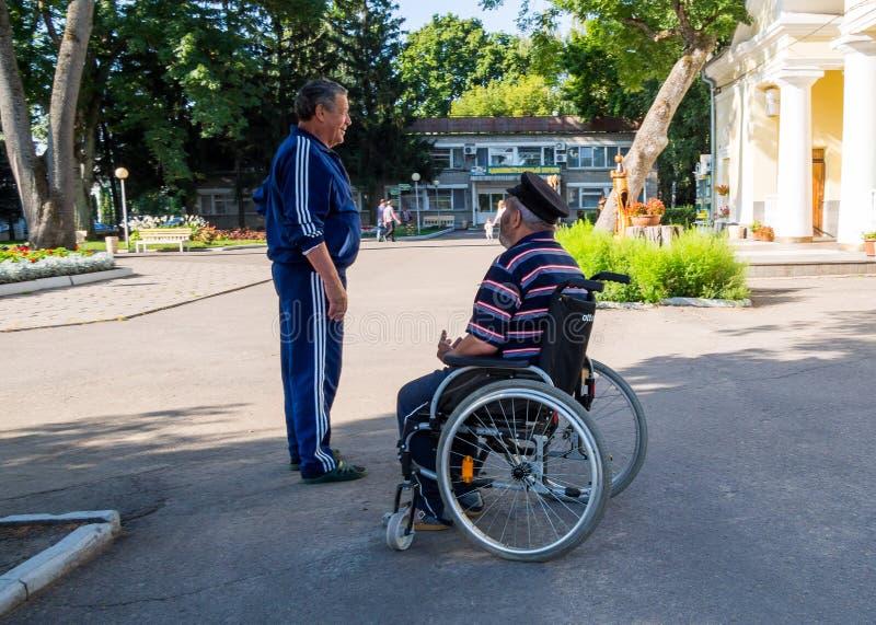 En man som talar med en äldre rörelsehindrad person i en stad, parkerar arkivfoton