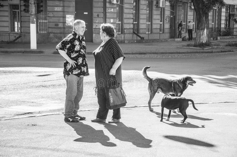 En man som talar till en kvinna på gatan royaltyfri foto