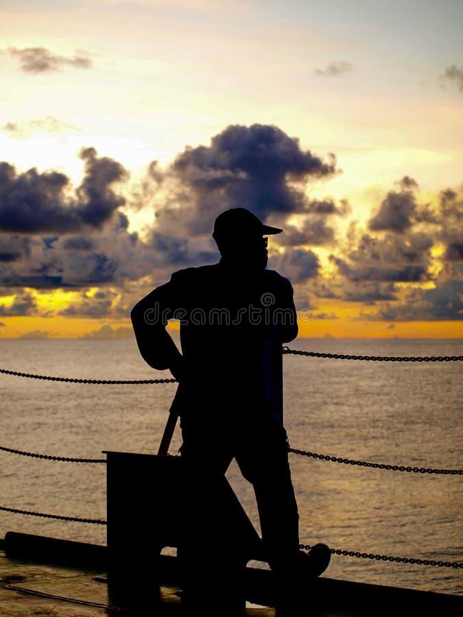 En man som tycker om solnedgångögonblick arkivbild